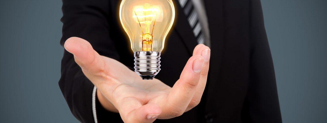 Business man holding light bulb